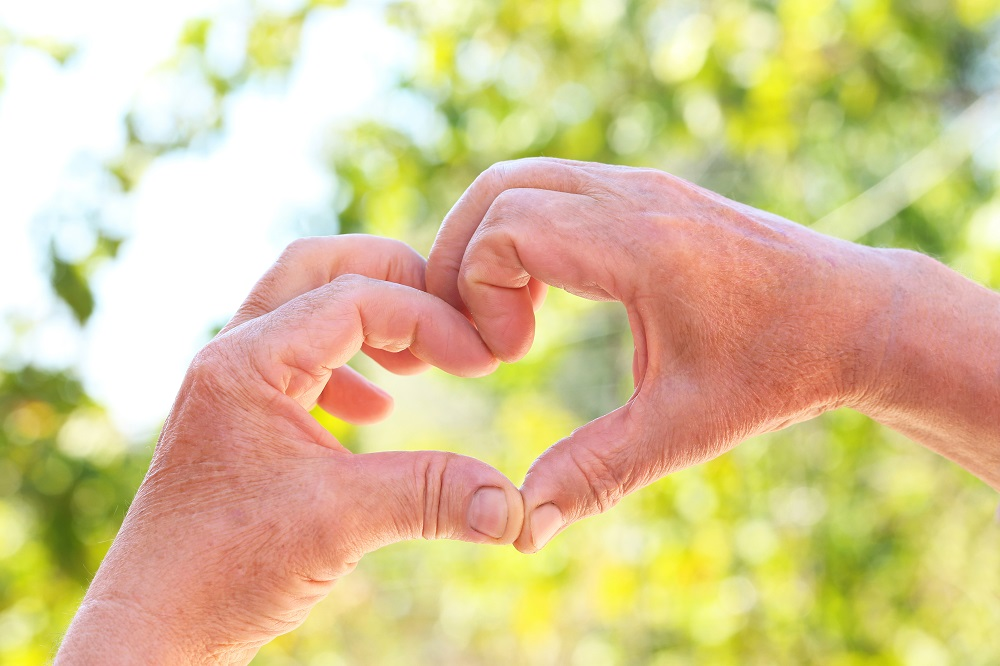 Hands of old senior showing heart